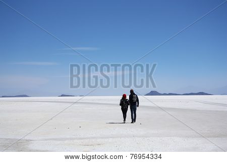 Tourists walk in a salt desert of Salar de Uyuni