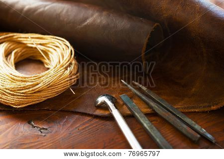 Leather craft. Leather and leather threading or sewing tools on a work table.