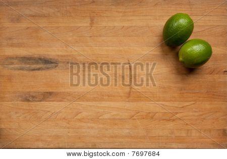 Limes On A Worn Butcher Block Cutting Board