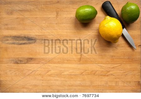Worn Butcher Block Cutting Board With Lemon And Limes