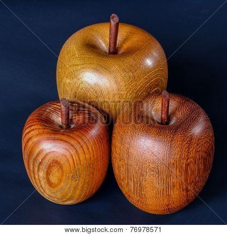 Three Wood Turned Apples On A Deep Blue Background.