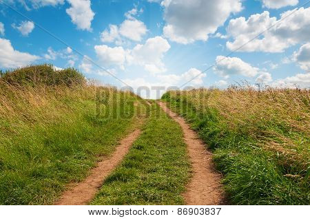 Grassy Path Facing Uphill With Blue Sky.