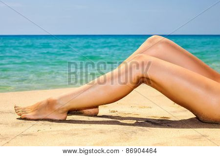 Woman's beautiful legs on the beach