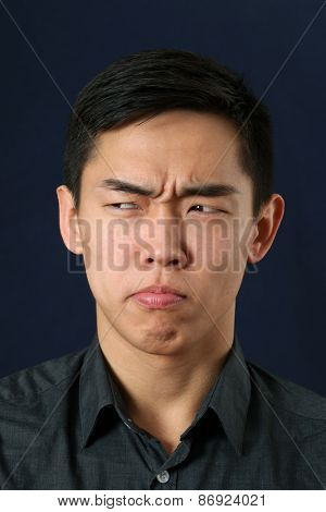 Young Asian man making face and looking sideways