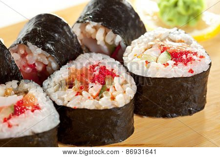 Japanese Cuisine - Sushi Roll with Salmon, Shrimps, Eel and Tobiko inside. Nori outside