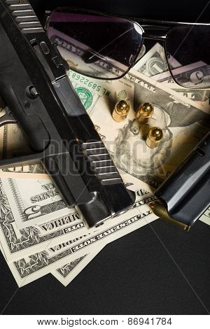 detail of gun with bullet on US dollar banknotes crime or corruption concept poster