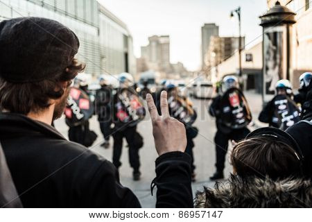 Man Making A Peace Sign In Front Of Cops