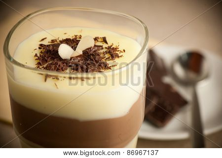 Mixed Chocolate And Vanilla Pudding Served In A Glass Decorated With Chocolate Pieces poster