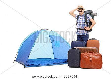 Baffled male tourist standing next to a tent and five huge briefcases isolated on white background poster