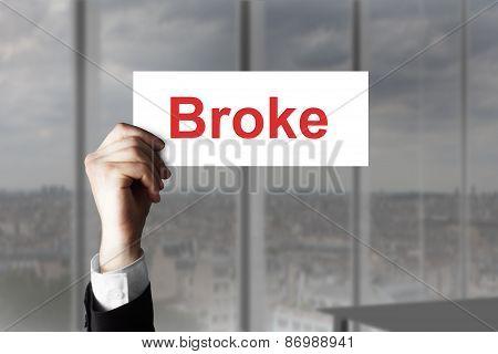 Businessmans Hand Holding Sign Broke