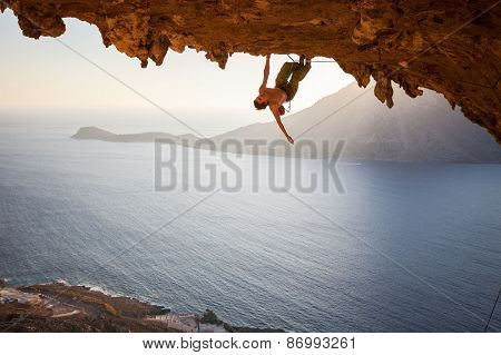 Male rock climber climbing along a roof in a cave at sunset poster