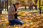 Young red-haired man sitting on the ground spangled with leaves in autumn park cutting maple leaves of colored paper by scissors and making them real by his imagination poster