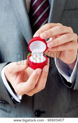 Engagement Ring In Hands. Man Making Proposal With Wedding Ring In Open Gift Box poster