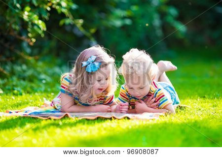 Two Kids Reading In Summer Garden