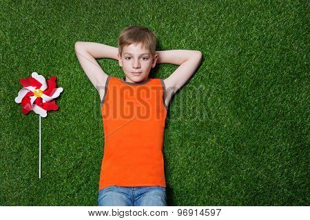 Boy lying with pinwheel  on green grass