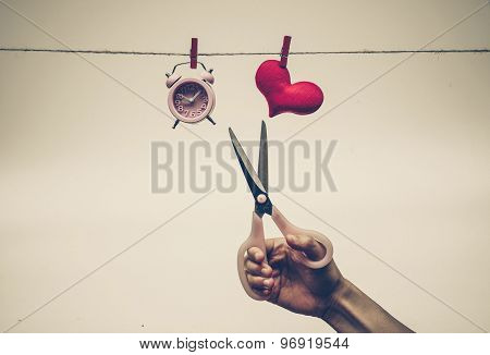 scissors cutting a rope hung with a clock and a red heart