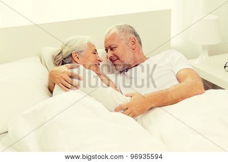 family, bedtime, resting, age and people concept - happy senior coupler lying in bad at home