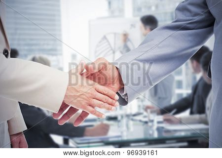 Close up of business people shaking their hands against business people in office at presentation