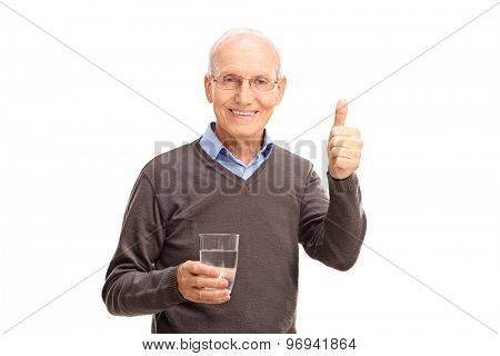 Studio shot of a senior man holding a glass of water and giving a thumb up isolated on white background