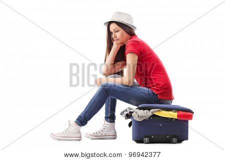 Sad young girl sitting on a briefcase full of clothes and thinking isolated on white background