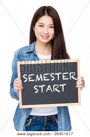 Young woman hold with chalkboard showing phrase of semester start
