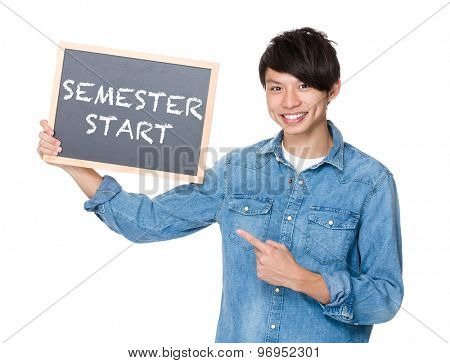 Asian man finger point to chalkboard and showing phrase of semester start