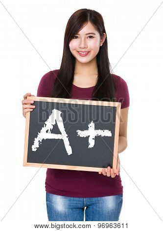 Asian woman with chalkboard showing mark A plus