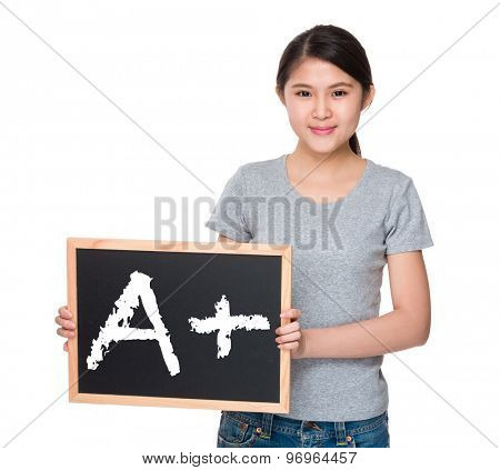 Young woman with the blackboard and showing A plus mark