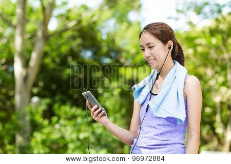 Sporty woman look at the cellphone with earphone