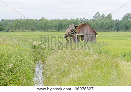 Tumbledown Barn On A Field With A Creek