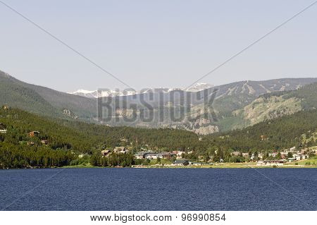 Barker Meadow Reservoir is foreground to Nederland in Colorado. Indian Peaks Wilderness behind town. Evergreens on slopes. poster