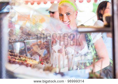 Woman eating candy apple at Oktoberfest wearing Dirndl