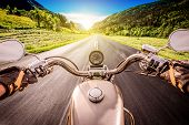 Biker driving a motorcycle rides along the asphalt road. First-person view. poster