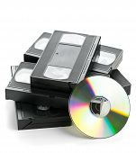 Heap of analog video cassettes with DVD disc - old movies backup or transfer concept poster