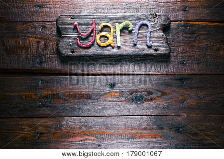 Knit shop background with title wood sign 'Yarn' of handmade colorful letters. Rustic wood board field