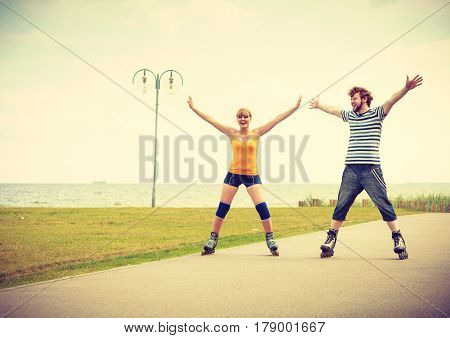 Holidays active people and friendship concept. Young fit couple on roller skates riding outdoors on sea shore woman and man together on the promenade