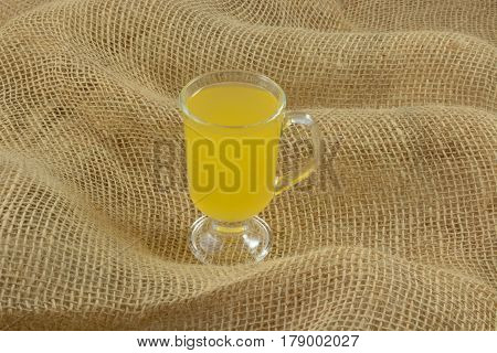 Yellow passionfruit fruit juice drink in glass on waves of burlap