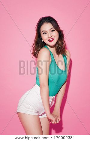 Summer Lady. Beautiful Asian Girl With Professional Makeup And Stylish Hairstyle On Pink Background.