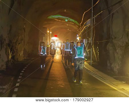 STOCKHOLM SWEDEN - MAR 25 2017: Rear view of many runners in reflex vest in a dark tunnel in the Stockholm Tunnel Run Citybanan 2017. March 25 2017 in Stockholm Sweden