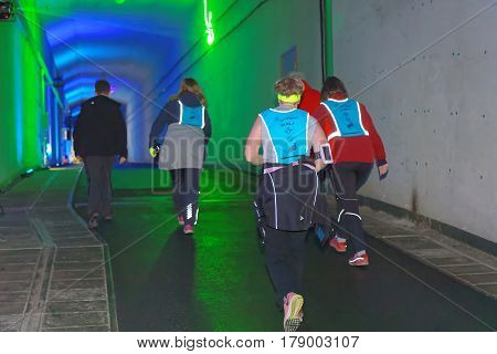 STOCKHOLM SWEDEN - MAR 25 2017: Rear view of seniors walking in a steep ascent in green lit tunnel in the Stockholm Tunnel Run Citybanan 2017. March 25 2017 in Stockholm Sweden