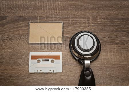 Retro audio tape and headphones on brown wooden background
