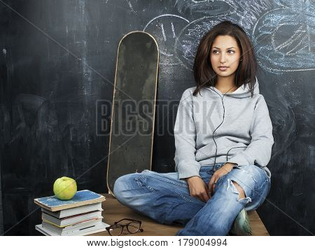 young cute teenage girl in classroom at blackboard seating on table smiling, modern hipster concept close up