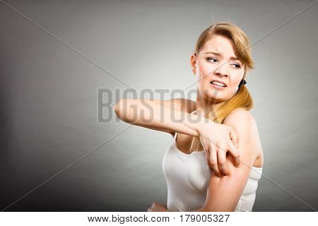 Woman Scratching Her Itchy Arm With Allergy Rash