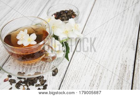A cup of jasmine tea with jasmine flowers on a wooden background