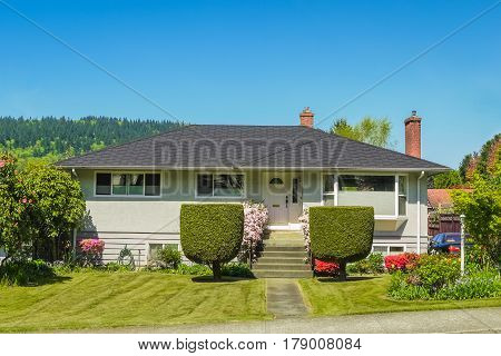 Average residential house with decorative bushes on the front yard