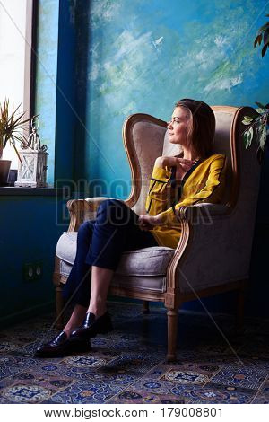 Low angle of a delightful young girl looking through the window while dreaming about something. Female in a yellow blouse looking sideward