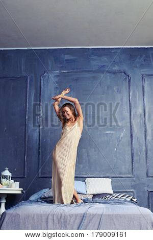 Full-length shot of a candid woman standing on the bed with arms crossed above her head.Carefree female in a beige pajamas having fun at home