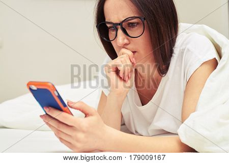 Close-up shot of preoccupied female looking at the telephone while lying on the bed. Female looking attentively at the screen of the telephone