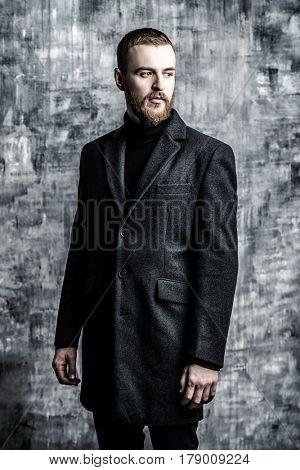 Fashion shot of a stylish brutal bearded man wearing coat. Studio shot over grunge background.
