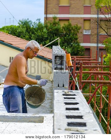 construction worker bricklayer installing red brick with trowel putty knife outdoors